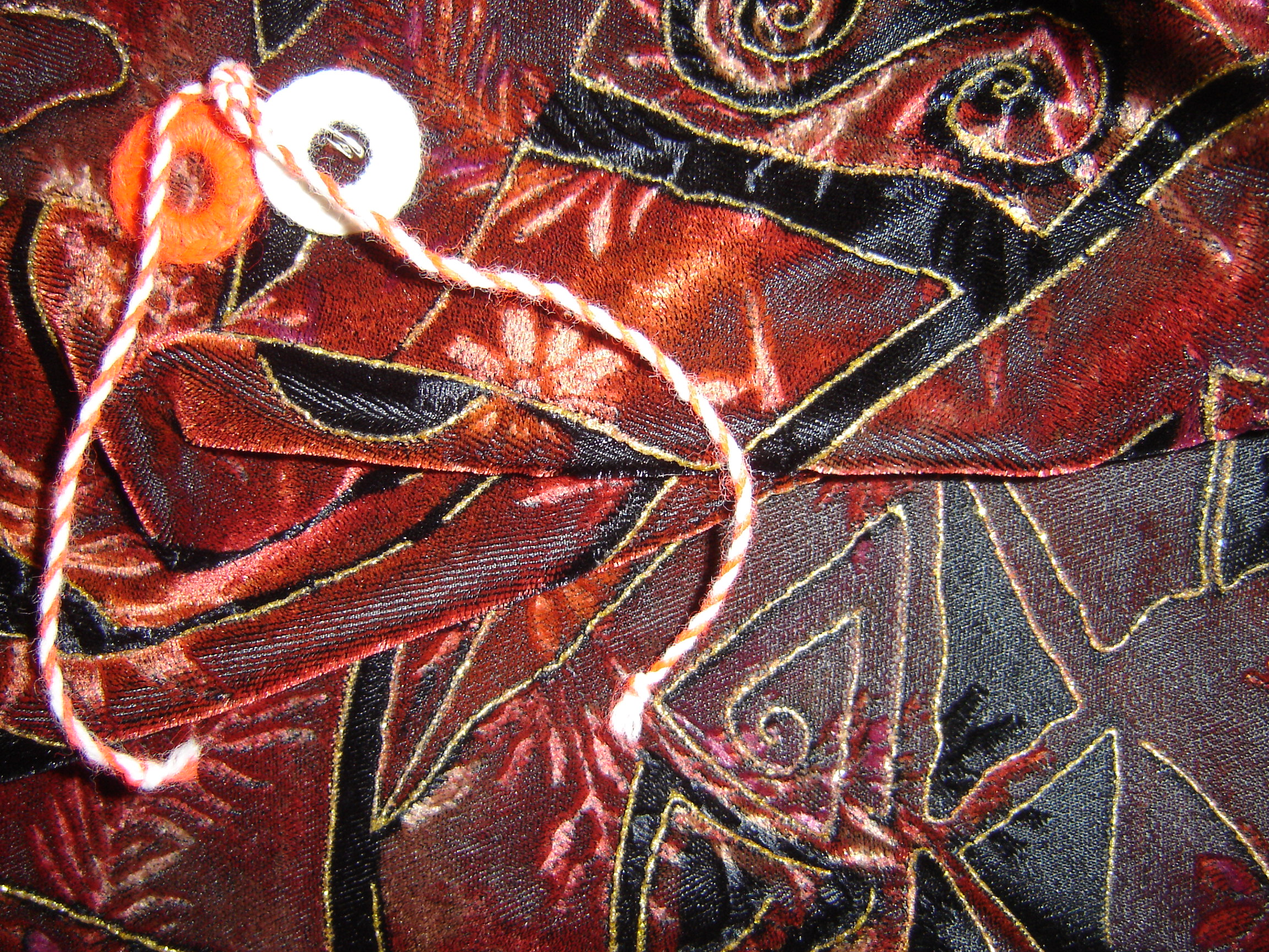 Martenitsa, pinned to a cropped velvet jacket