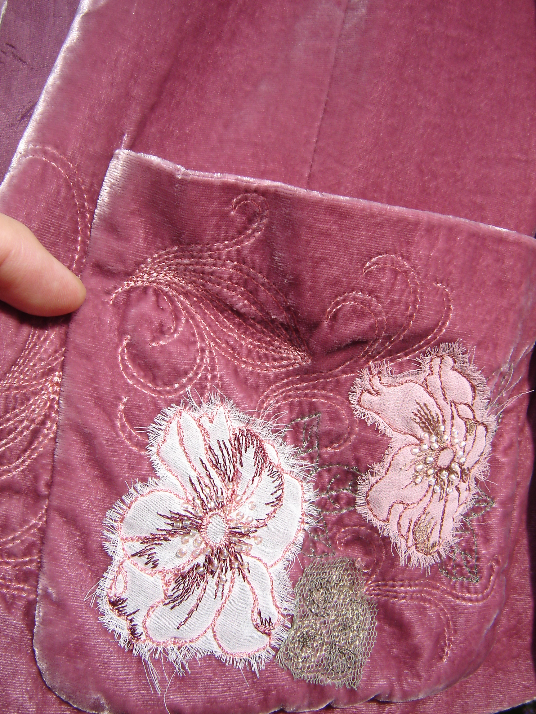 Pink cropped velvet jacket with appliqued flowers.