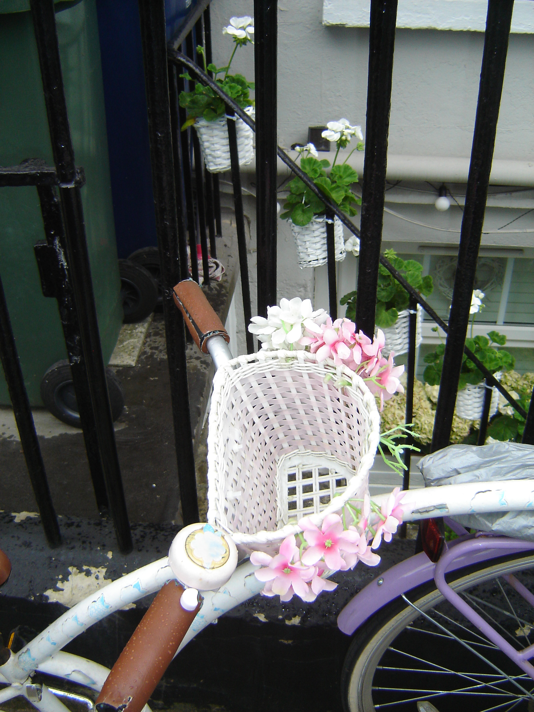 A bicycle basket decorated with pink plastic flowers