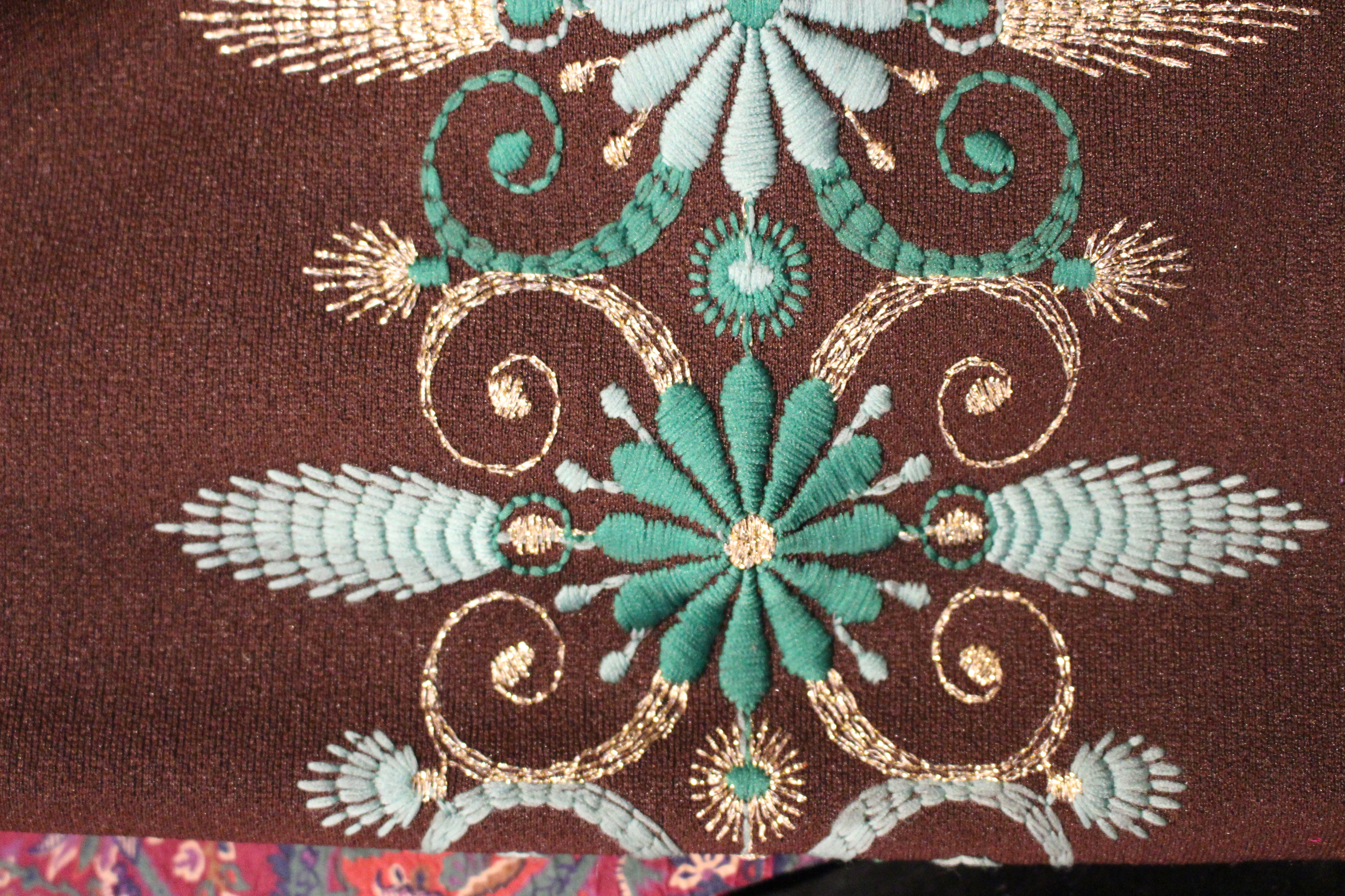 Green and gold embroidered brown coat, in Unicorn, 5 Ship Street, Oxford